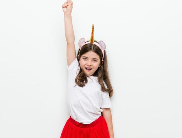 Маленькая кавказская девочка с костюмом и аксессуарами веселится
