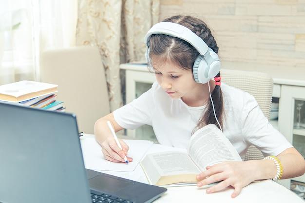 コンピューターでビデオチュートリアルを見ているヘッドフォンを持つ小さな白人の女の子。コンピューターでのオンライン学習、ホームスクーリングの概念。