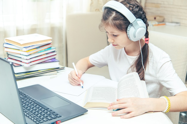 Little caucasian girl with headphones watching a video tutorial on the computer. online learning on computer, home schooling concept.