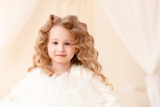 長い巻き毛の白い髪と茶色の目を持つ小さな白人の女の子