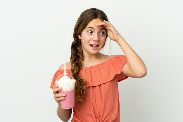 흰색 배경에 격리된 딸기 밀크셰이크를 든 백인 소녀는 옆을 바라보면서 깜짝 제스처를 취한다