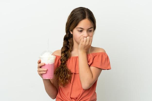 Маленькая кавказская девушка с клубничным молочным коктейлем на белом фоне с сомнениями