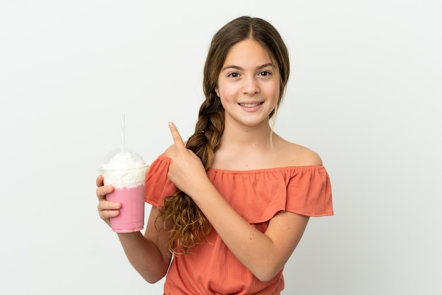 다시 가리키는 흰색 배경에 고립 된 딸기 밀크 쉐이크와 어린 백인 소녀