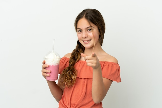행복 한 표정으로 앞을 가리키는 흰색 배경에 고립 된 딸기 밀크 쉐이크와 어린 백인 소녀