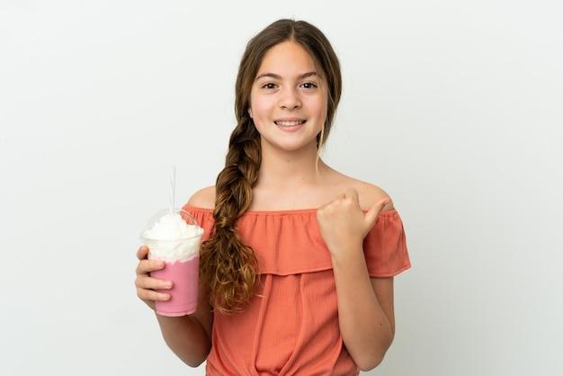 흰색 배경에 격리된 딸기 밀크셰이크를 들고 있는 백인 소녀는 제품을 제시하기 위해 측면을 가리키고 있습니다.