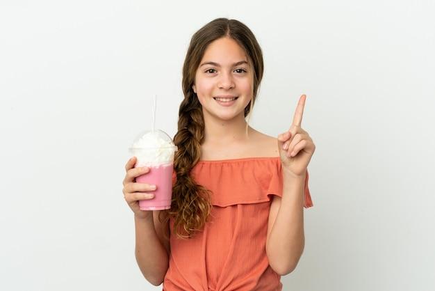 좋은 아이디어를 가리키는 흰색 배경에 고립 된 딸기 밀크 쉐이크와 어린 백인 소녀