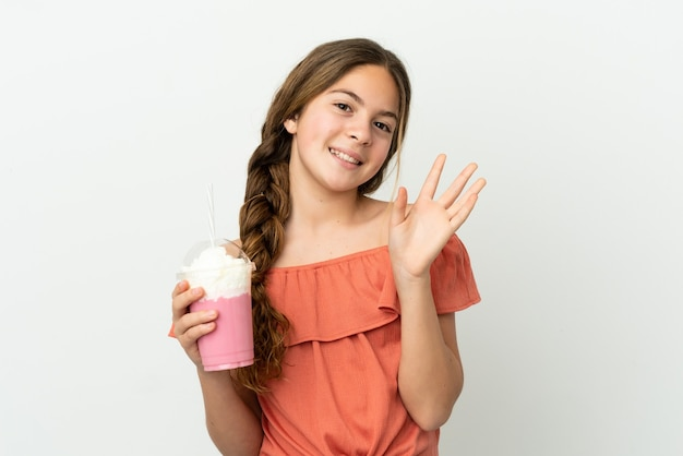 幸せな表情で手で敬礼する白い背景に分離されたイチゴミルクセーキと小さな白人の女の子