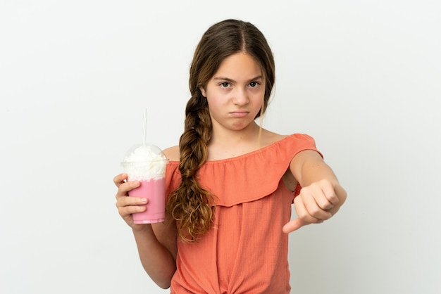 흰색 배경에 격리된 딸기 밀크쉐이크를 든 백인 소녀는 부정적인 표정으로 엄지손가락을 아래로 내립니다.
