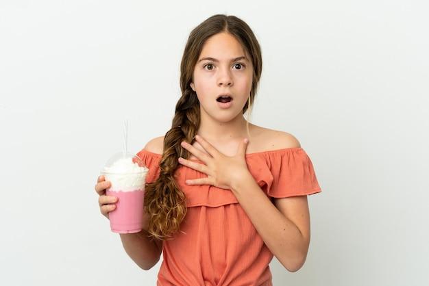 흰색 배경에 격리된 딸기 밀크셰이크를 든 백인 소녀는 오른쪽을 보고 놀라고 충격을 받았습니다.