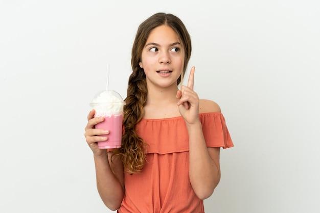 흰색 배경에 격리된 딸기 밀크셰이크를 든 백인 소녀는 손가락을 가리키는 아이디어를 생각하고 있다