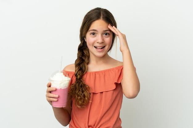 Маленькая кавказская девушка с клубничным молочным коктейлем на белом фоне с удивленным выражением лица