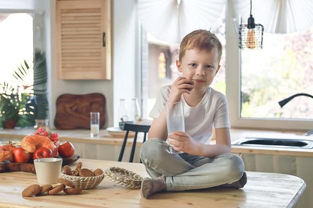 작은 백인 웃는 소년은 식탁에 앉아 우유와 함께 오트밀 쿠키를 먹습니다