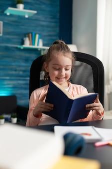 本を読むページを保持している小さな白人学生