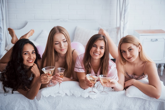 A little champagne will not interfere. joyful girls in the nightwear lying on the bed in white room and have celebration