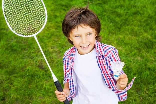 リトルチャンピオン。緑の芝生の上に立っている間バドミントンラケットとシャトルコックを保持している幸せな少年の上面図
