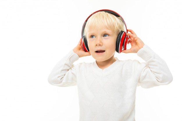 Little charming blond baby listening to music on headphones on a white background