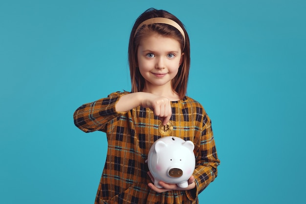 Little charming girl kid holding piggy bank and putting bitcoin coin in it