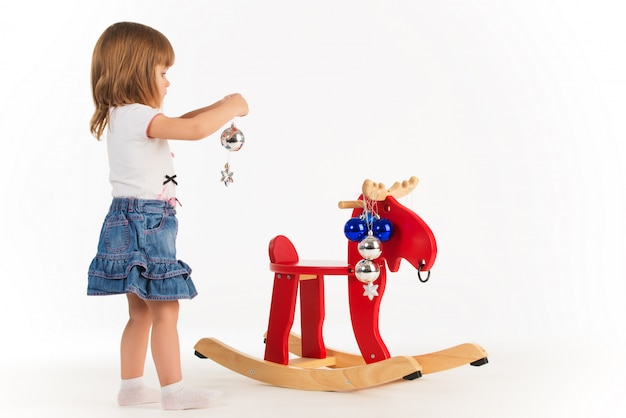 Little charming girl plays with a wooden elk