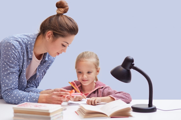 Little charming girl sits at table, has difficult homework task, her mother trying to help daughter and explains mathematics rules, uses reading lamp for good vision. education concept.