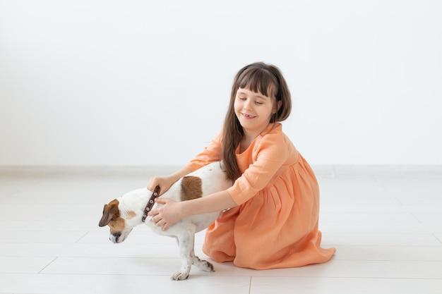 長いドレスを着た黒髪の小さな魅力的な女の子が犬のジャックラッセルテリアの隣に座っています