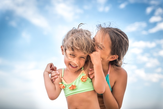 Маленькие очаровательные сестры шепчут что-то друг другу на ухо во время летних каникул в теплый летний день на фоне голубого неба.