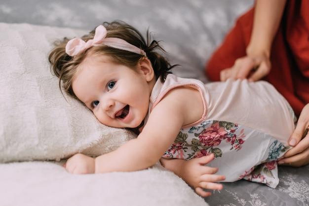 Маленькая веселая девочка лежит на кровати, пока ее мать одевает ее.