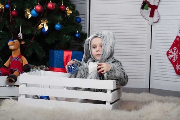 新年のツリーと新年のバニー衣装で小さな陽気な男の子