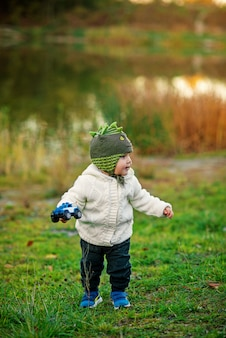 A little cheerful boy in a knitted hat and warm clothes playing with a toy car on a green grass near the lake. happy childhood concept.