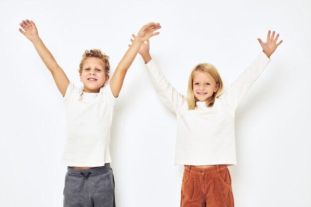 Маленькие веселые веселые друзья улыбаются, создавая повседневную одежду на светлом фоне. фото высокого качества