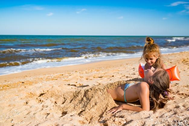 밝고 따뜻한 여름날 해변에서 놀면서 쾌활한 어린 소녀가 누나를 모래에 묻습니다. 활동적인 게임과 휴일의 개념. 카피스페이스