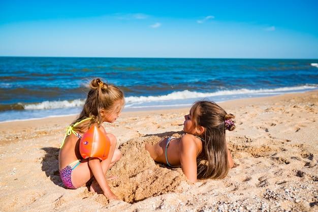 명랑 소녀는 화창한 따뜻한 여름날에 바다 해변에서 노는 동안 그녀의 누나를 모래에 묻어