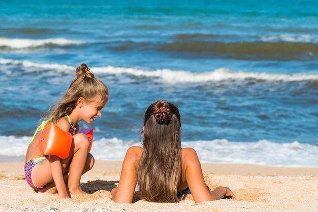 晴れた暖かい夏の日に海沿いのビーチで遊んでいる間、小さな陽気な女の子は彼女の姉を砂に埋めます