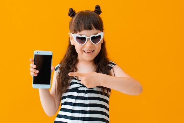 Маленькая жизнерадостная девочка в солнечных очках с сердцем на желтой стене указывает пальцем на экран смартфона. понятие о мобильных сервисах и приложениях. лето, интернет, паутина