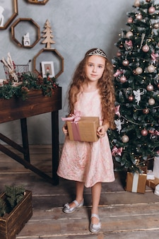 Little cheerful girl in christmas decoration with tea at cozy home with colorful new year lights