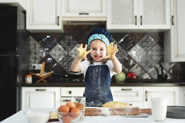 명랑 소녀 앞치마와 요리사의 모자에 부엌에서 그녀의 손으로 반죽 반죽.