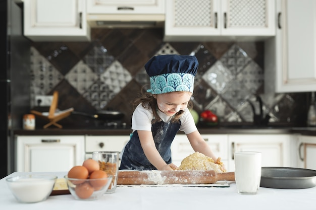 Little cheerful girl kneads dough with her hands in the kitchen
