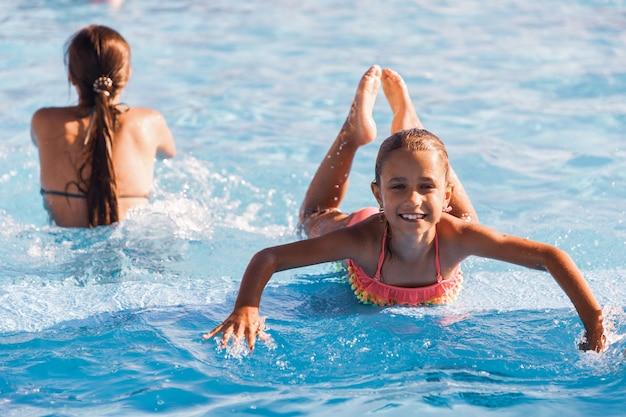 澄んだ澄んだ水とプールで遊んで、カメラに笑みを浮かべて見ている小さな陽気な女の子