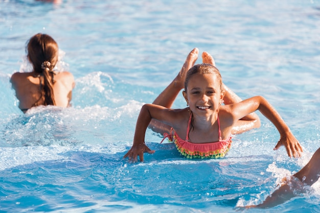 맑고 맑은 물로 수영장에서 놀고 카메라를 웃고있는 명랑 소녀