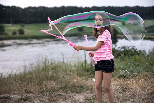 小さな陽気な女の子は、自然の中で大きなシャボン玉で遊んでいます。