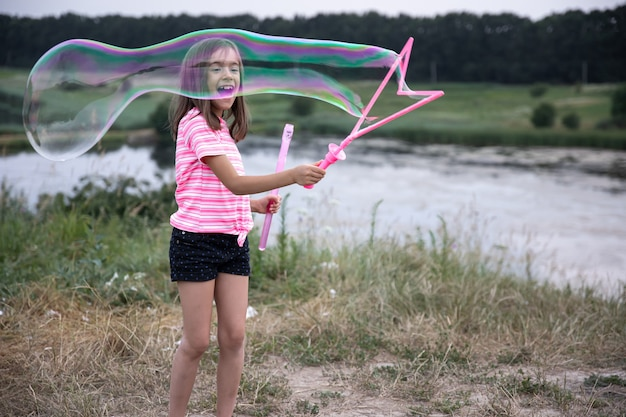 Little cheerful girl plays with big soap bubbles in nature.