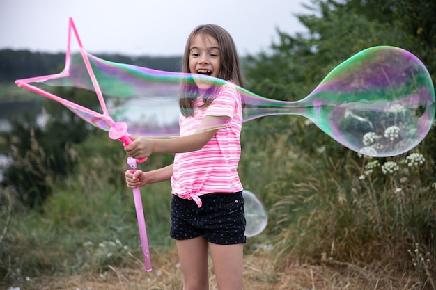 La piccola ragazza allegra gioca con grandi bolle di sapone in natura.