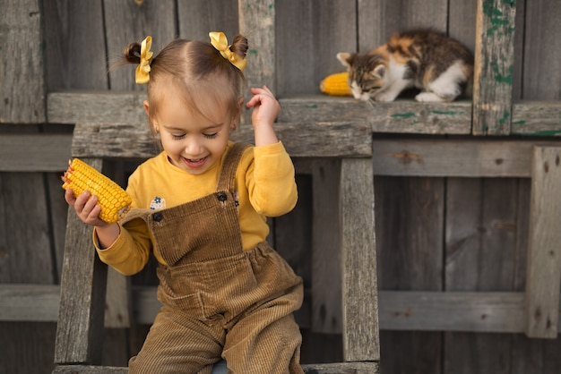 A little cheerful girl sits on a wooden ladder and eats corn. the kitten is sitting next to the child.