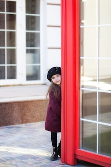 Little cheerful girl standing near the red phone booth in a burgundy coat and beret. london red telephone booth. spring. autumn. with the international women's day. since march 8!
