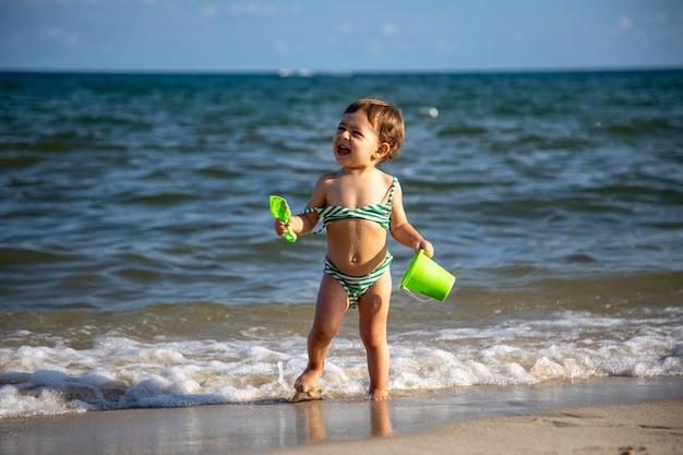 小さな陽気な幸せな男の子は、バケツとシャベルで海の波で遊んでいます。