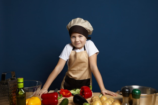 Piccolo chef ragazzo in copricapo e grembiule che prepara cibo sano, guardando e sorridendo alla telecamera mentre si trova al tavolo della cucina, tagliare le verdure per la cena. infanzia, cucina e vegetarianismo