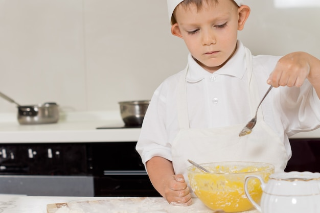 Little chef checking the consistency of his batter