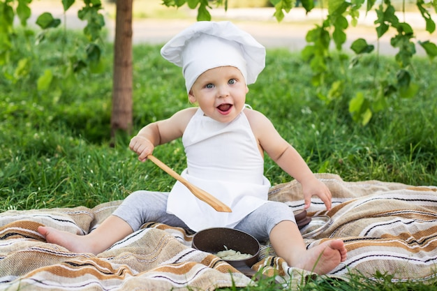 Little chef cooks and eats pasta on a picnic outdoors