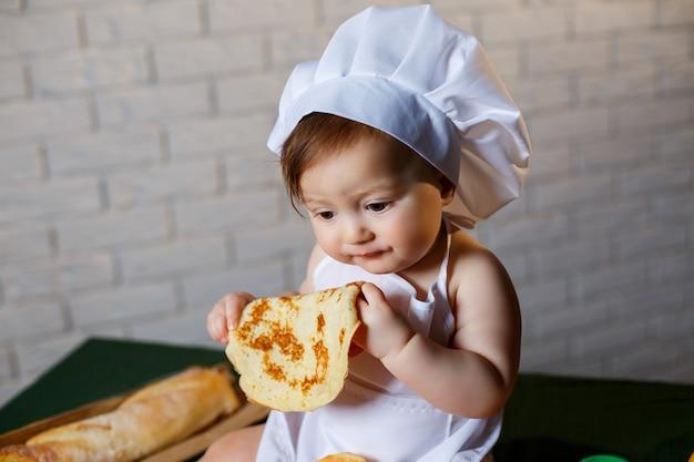 小さなシェフ。ペストリー、パン、パンでシェフに扮した小さな子供