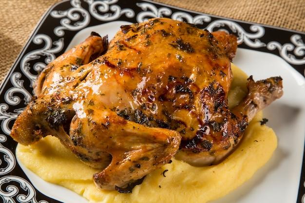 나무 테이블에 폴렌타와 작은 치킨 요리