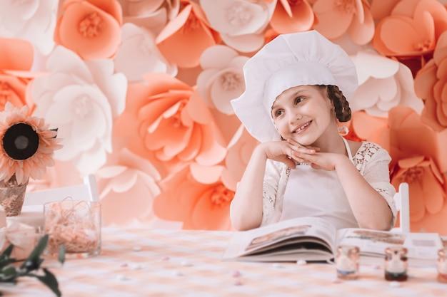 부엌에 작은 수석. 수석 모자에 매력적인 어린 소녀는 저녁 식사를 요리 할 준비가 식탁에 서